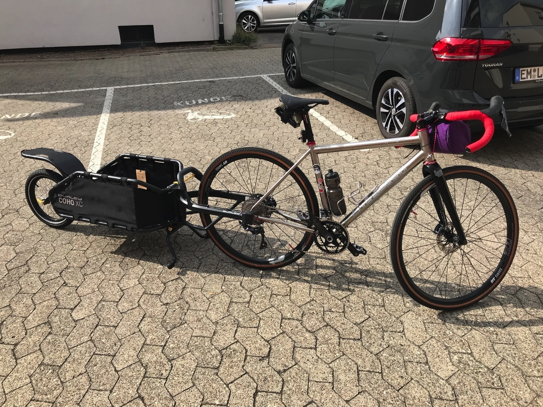 Drop bar, titanium gravel bike with a single-wheel cargo trailer attached to the rear axle in a parking lot.