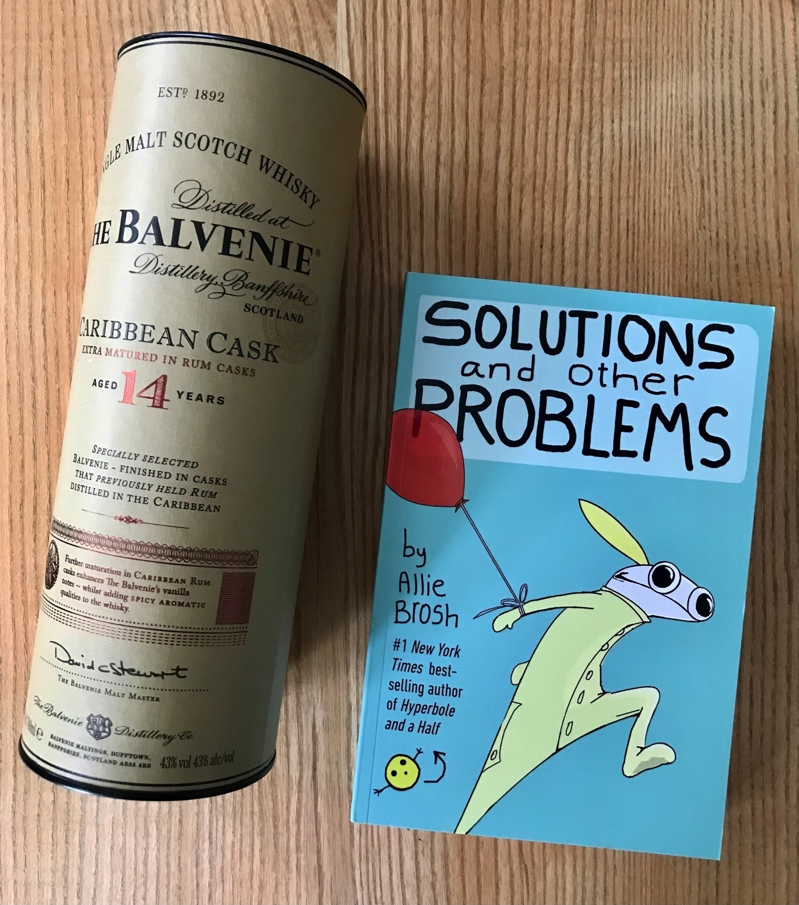 Tubublar packaging containing a bottle of Balvenie Caribbean Cask whisky and the new book by Allie Brosh on a wooden table.
