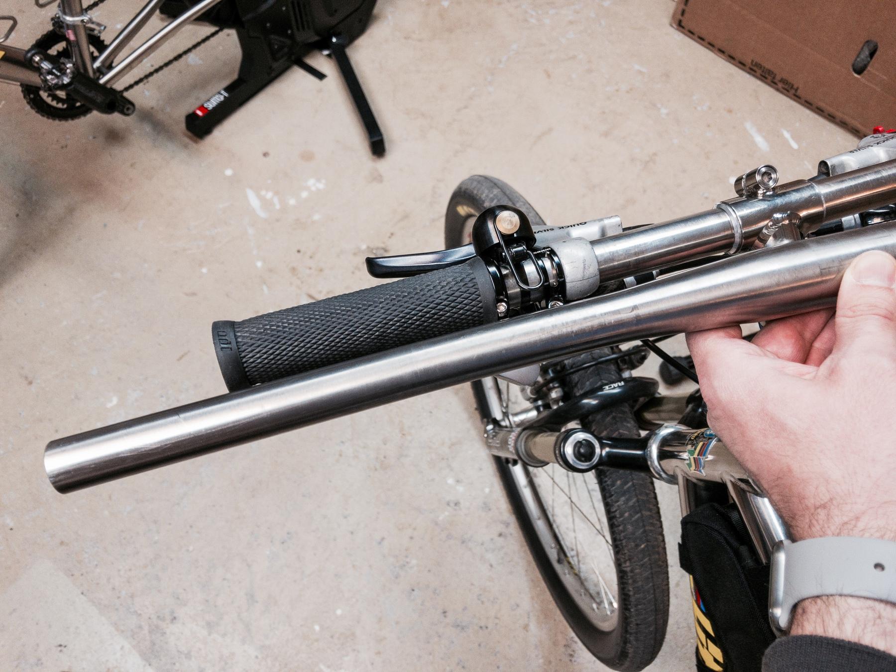 Wide titanium handlebar held over a much narrow handlebar on a bike in a workshop.