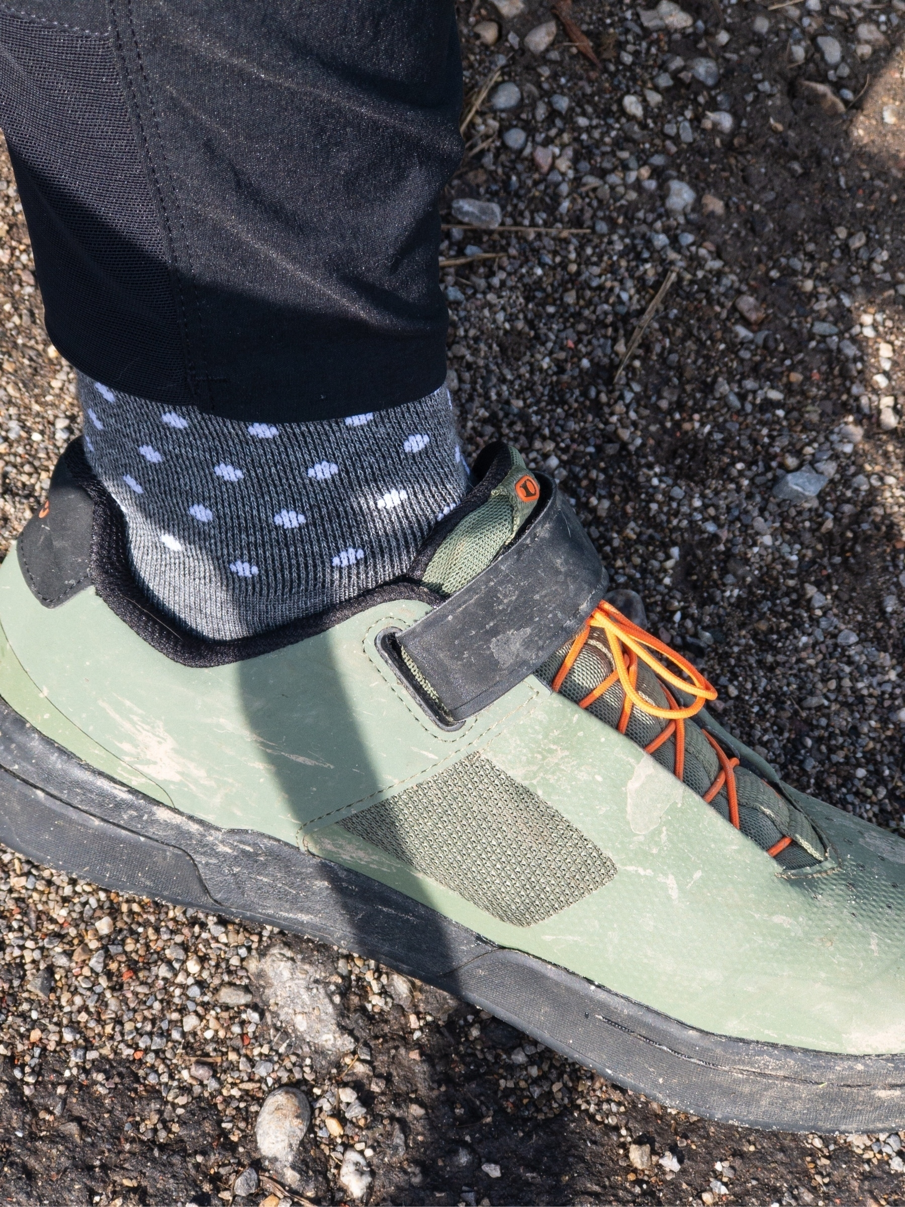 Close-up (from the side) of grey socks with white polka dots in olive green mountain bike shoes.