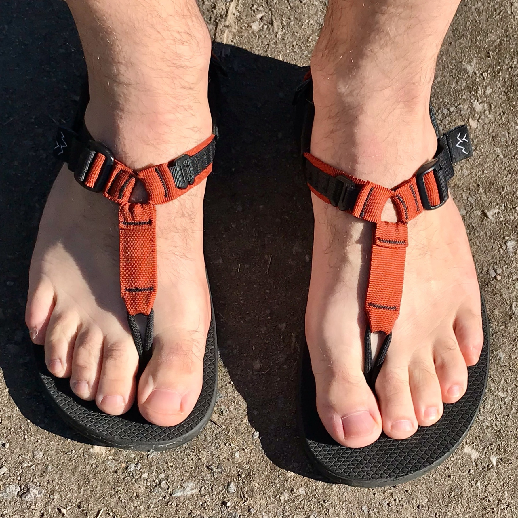 A pair of human, slightly hair feet, very pasty, in sandals with orange straps.