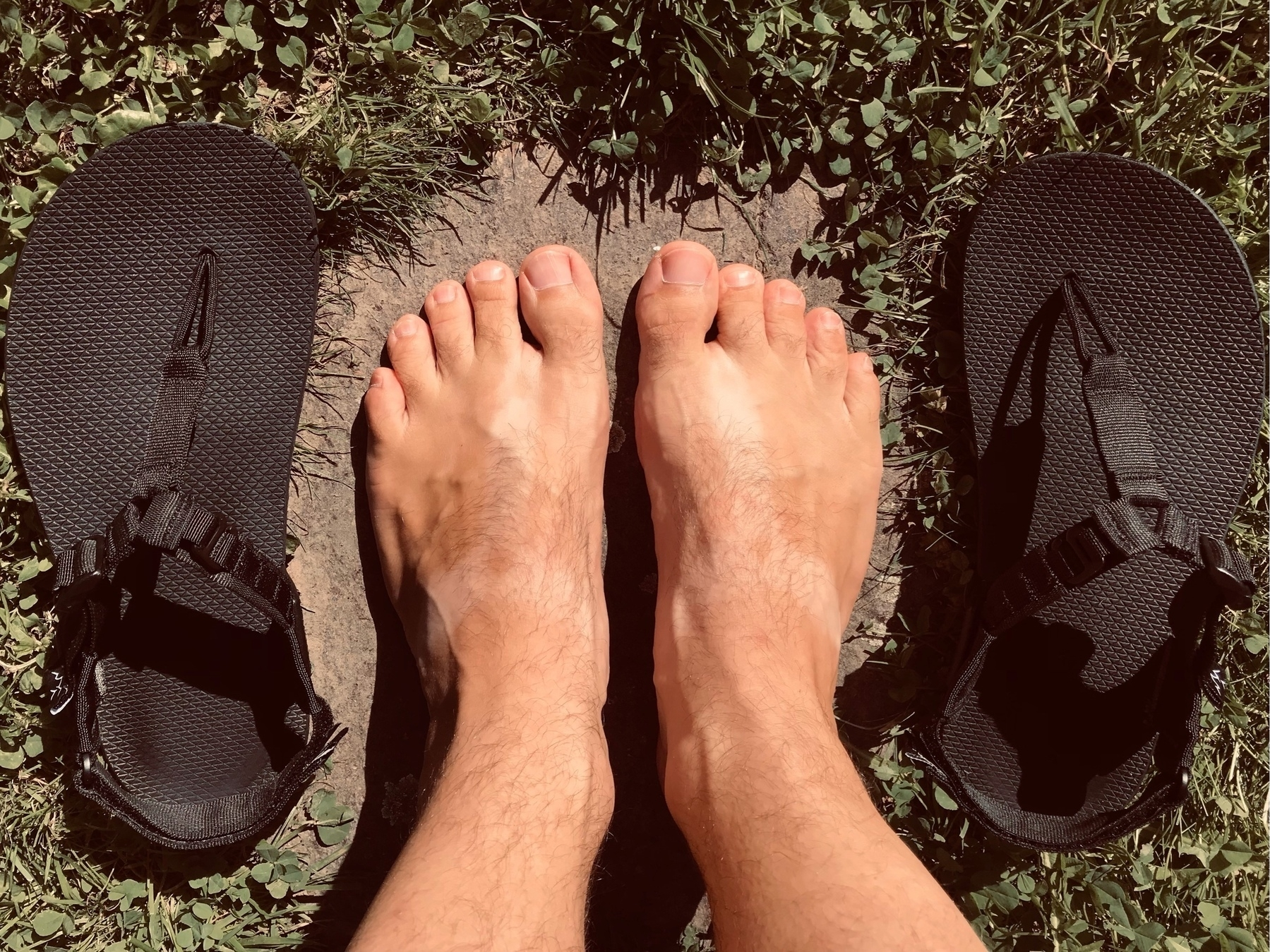 Top view of lightly tanned bare feet with tan lines in the shape of sandal straps. The black sandals that caused those tan lines laying to the left and right of the feet.