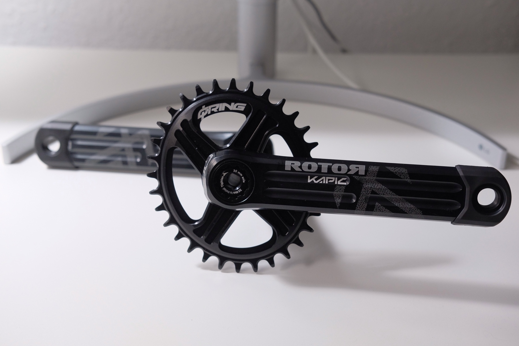 Aluminium single chainring crankset with an oval chainring on a white table in front of the foot of a monitor.